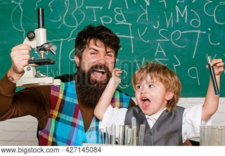 Teacher Helping Kid With Their Homework In Classroom At School. Child And Teacher In The Class Room.