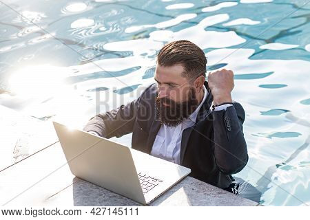 Smart Man Using A Laptop Near The Pool. Business Man In Suit With Notebook On Swimming Pool. Funny B