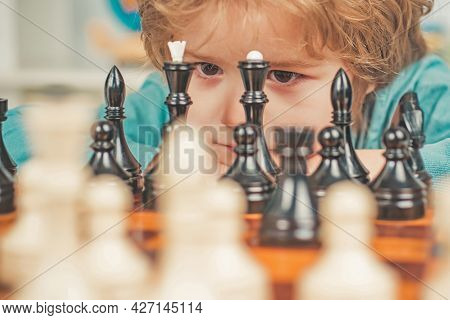 Happy Child And Childhood. Little Clever Boy Thinking About Chess. Cute Little Boy Playing Chess.