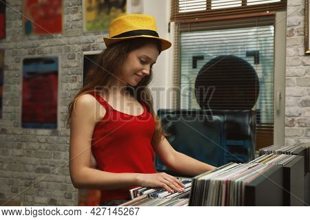 Young Woman Choosing Vinyl Records In Store