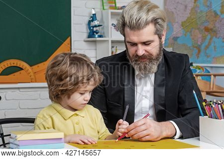 Father Teaching Son. Funny Little Child With Father Having Fun On Blackboard Background. Supporting