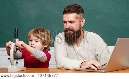 Man Teacher Play With Preschooler Child. Homeschooling. Teacher And Schoolboy Using Laptop In Class.