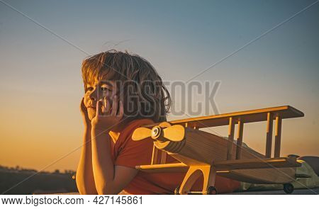 Child Dreams And Imagination Concept. Dreaming Child Playing With Toy Wooden Airplane Against Summer