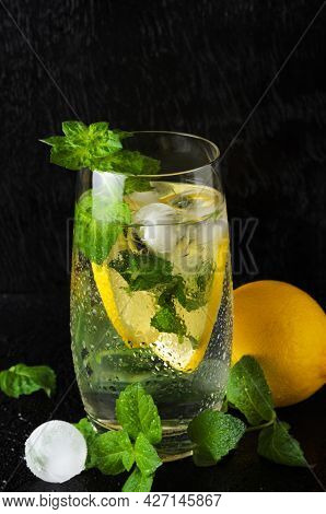 A Large Glass Of Water With Lemon, Mint Leaves And Ice, Covered With Water Droplets. Lemonade On A B