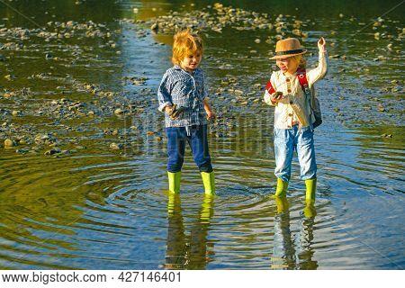 Children Throw Stones At The Stony River. Beautiful Children Throws A Rock At The River. Skipping Ro