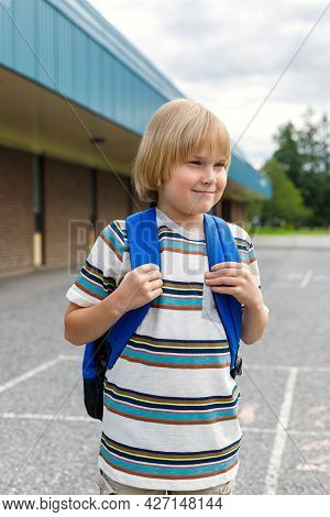 Small Smiling Schoolboy Standing At School Yard, Carrying Backpack. Back To School Concept.