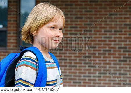 Little Schoolboy Walking To School, Carrying Backpack. Back To School Concept. Student Against Brick