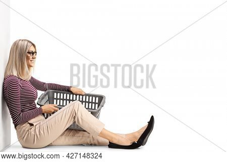 Woman with a laundry basket sitting and leaning on a wall isolated on white background