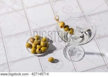 Martini Cocktail With Olives On The Tiled Table. An Alcoholic Classic Drink With Ice In An Elegant G