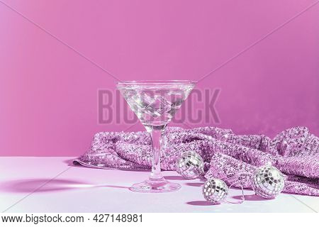 Martini With Ice In An Elegant Glass Of Disco Balls On A Shiny Pink Background. Fashionable Bright D
