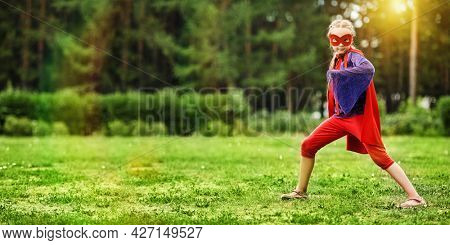 A cute girl in a superhero costume emotionally poses on lawn against the background of a summer forest in the open air. Sunny summer days. Summer holidays. Games in the park.