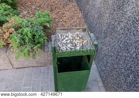Smoking area next to the office building. The cigarette butts are in the trash. Maintaining cleanliness on the street.