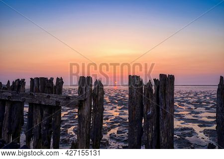 View Of The Wadden Sea During Sunset, At Low Tide. A Colorful Dramatic Sky. Wooden Posts As A Silhou