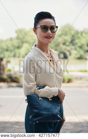 Elegant Well-dressed Mature Woman In Silk Blouse And Sunglasses Standing Outdoors With Leather Bag I