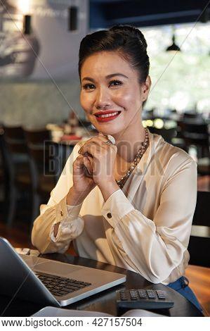 Portrait Of Smiling Elegant Female Restaurant Owner Working On Laptop