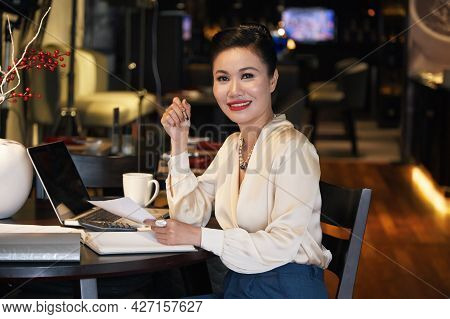 Portrait Of Beautiful Smiling Businesswoman Working At Restaurant Table And Signing Documents