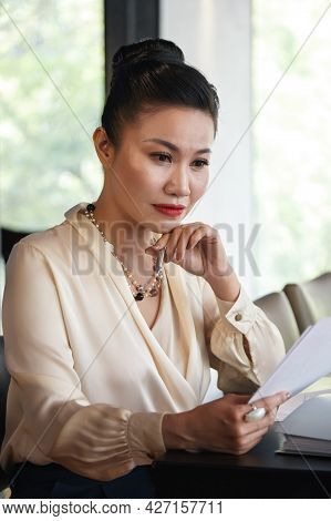 Serios Pensive Female Entrepreneur Reading Document With Important Information