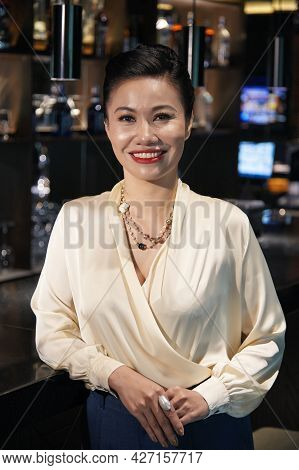 Attractive Smiling Woman In Silk Blouse Standing At Bar Counter In Restaurant