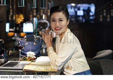 Beautful Smiling Female Restaurant Manager Working On New Menu, She Is Sitting At Bar Counter And Wo