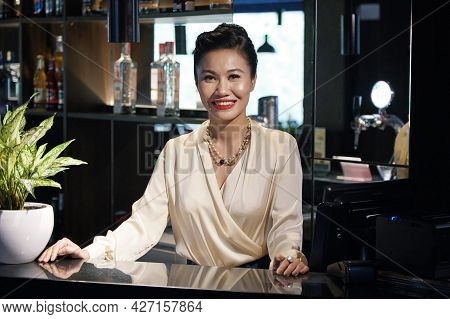 Portrait Of Smiling Elegant Restaurant Owner In Silk Blouse Standing Behid Bar And Looking At Camera