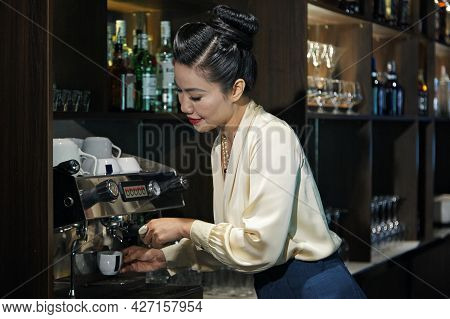 Female Restaurant Manager Making Cup Of Coffee To Ged More Energy For The Rest On The Night