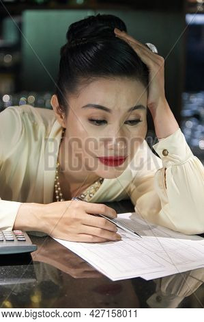 Tired Restaurant Manager Leaning On Bar Counter And Analyzing Data In Sales Reports