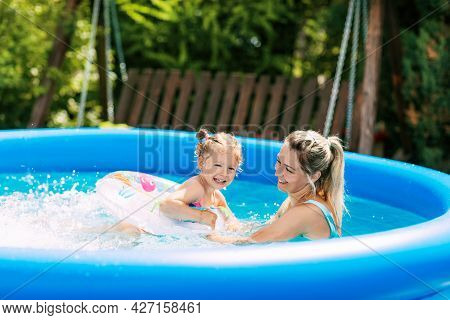 Cheerful Healthy Mother And Daughter Play In Swimsuits In The Pool. Time Together, Summer Time, Vaca