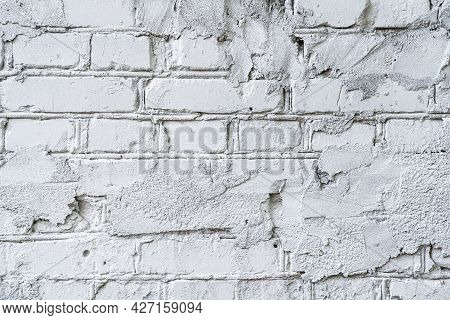 Closeup Of An Old Brick Wall, Painted White. The Brickwork Is Uneven, There Are Sloppy Marks Of Repa