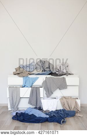 Chest Of Drawers And Pile Of Dirty Laundry In Living Room - Copy Space Over Grey Wall Background
