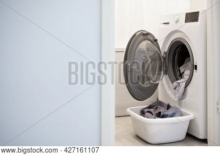 Washing Machine And Laundry Basket In Bathroom, Copy Space Over Blue Wall Background