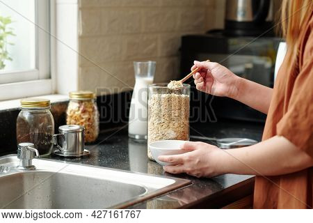 Woman Standing At Kitchen Counter And Putting Spoon Of Quick Oatmeal In Bowl