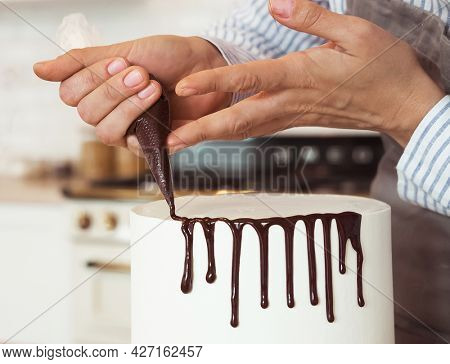 woman is decorating the cake with chocolate, hands close up
