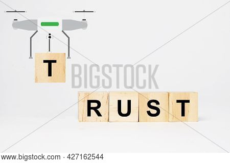A Picture Of A Drone Carrying T Word Wooden Block. Insight Rust Wooden Block. Building Trust Concept