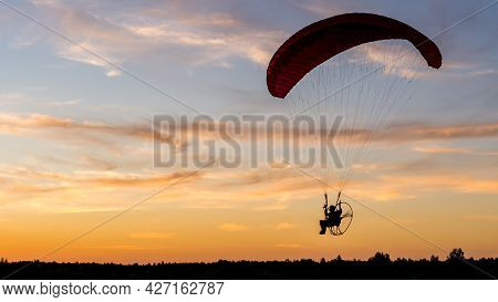 Powered Paragliding Pilot Silhouette With Back-mounted Motor (paramotor) During Sunset