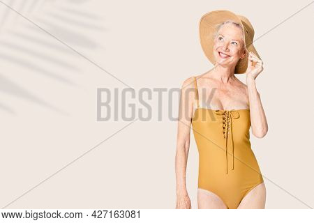 Senior woman in yellow swimsuit and sun hat summer fashion