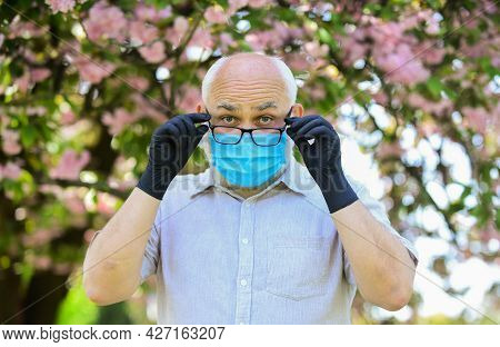 Senior Man Wearing Face Mask And Gloves Outdoors. How To Help Senior Citizens. Seniors Are Especiall