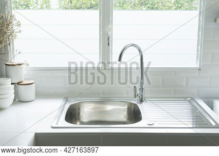 Close Up Of Modern Sink In Home Kitchen By The Window.