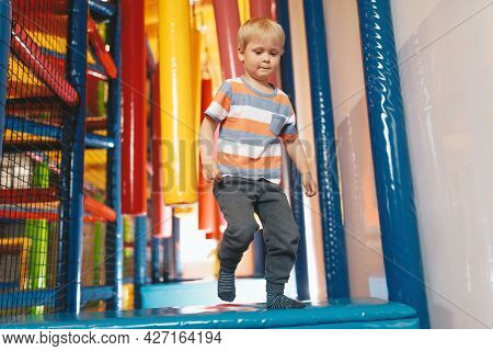 Happy Little Boy Playing In Indoor Playground On Jumping Trail. Kid Jumping On Playground Cushions.