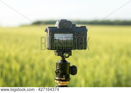 A Camera With A Lens On A Tripod, Ready For Taking Photos Or Videos In Nature. Photographing And Fil