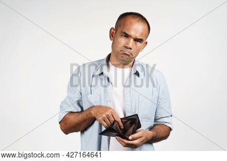 Upset Mature Man Holding And Looking Inside His Empty Wallet On White Background. Financial Crisis,