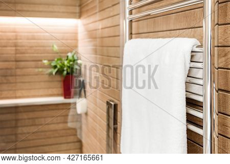 Wooden Bathroom Interior With Heated Towel Rail And White Towel On It.
