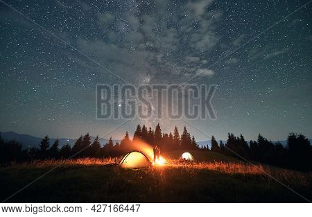 Fantastic View Of Night Starry Sky Over Grassy Hill With Illuminated Camp Tents And Couple Near Camp