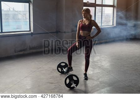 Full Body Of Strong Confident Athletic Female Standing Near Barbell While Preparing For Weightliftin