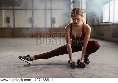 Full Body Of Determined Young Athletic Female In Activewear Doing Side Lunge Exercise With Heavy Dum