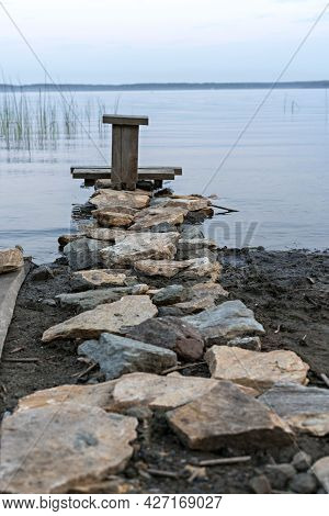 Meditation Area On The Lake, Stone Path And Wooden Seat, Contemplating The Sunset Or Daybreak