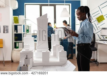 African American Architect Woman Working On Tablet Looking At Building Model Maquette. Professional