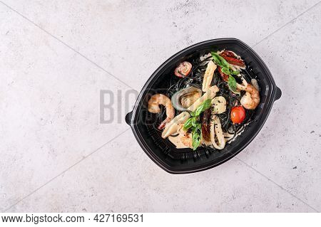 Black Spaghetti Nero With Seafood, Tomatoes And Basil In Black Plastic Container On Light Background