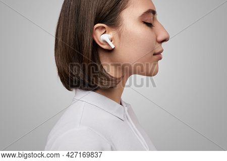Side View Of Calm Young Female With Eyes Closed Listening To Music With True Wireless Earbuds Agains