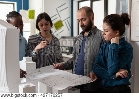 Team Of Multi Ethnic Architects Designing Blueprint Plan For Construction Project Design. Workers An