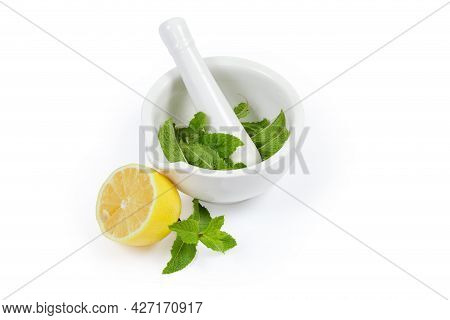 Fresh Spearmint Leaves In The Porcelain Kitchen Mortar With Pestle And Half Of Lemon On A White Back